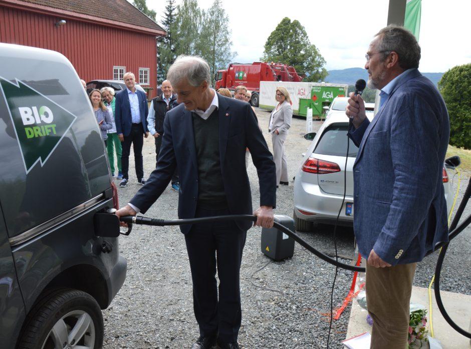 Jonas Gahr Støre fyller tanken, mens Erik Eid Hohle informerer om biodrivstoffstasjonen.